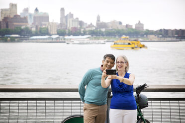 Happy mature couple taking selfie while standing on promenade by river in city - CAVF15060