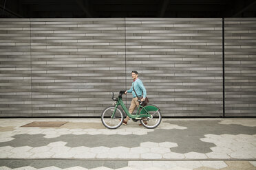 Side view of mature man walking with bicycle on footpath by wall - CAVF15063