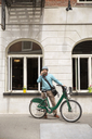 Mature man using smart phone while standing with bicycle against building - CAVF15066