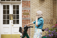 Side view of mature woman using smart phone against building - CAVF15069