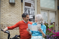 Happy mature couple reading road map while standing with bicycle outside building - CAVF15072