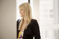 Thoughtful businesswoman standing in creative office - CAVF15087