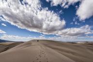 Distant view of people leaving behind footprints in desert - CAVF15153