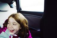 Happy girl sitting by window in car - CAVF15186