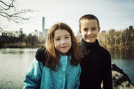 Portrait of smiling brother with arm around sister at lake in park - CAVF15189