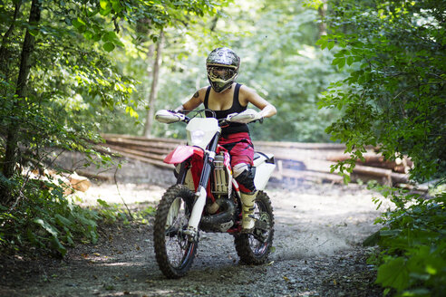 Young female riding motorcycle on dirt road in forest - CAVF15234
