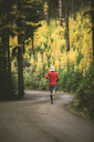 Rear view of man jogging on road amidst trees during autumn - CAVF15249