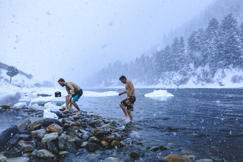 Men walking on stones in river during snowfall - CAVF15264