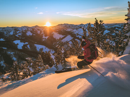 Woman skiing on snow slope during sunset - CAVF15273