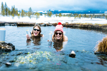 Portrait of happy friends with drink cans enjoying in lake - CAVF15288