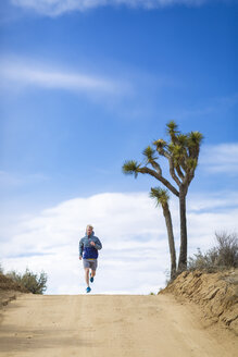 Male hiker running on road at Joshua Tree National Park against sky during sunny day - CAVF15324
