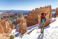 Rear view of hiker standing on snow covered mountain at Bryce Canyon National Park - CAVF15333