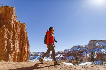 Hiker walking on mountain against clear sky at Bryce Canyon National Park during winter - CAVF15336