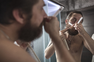 Portrait of bearded man looking at his mirror image while shaving - VPIF00386