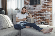 Man with cell phone relaxing on the couch at home - VPIF00389