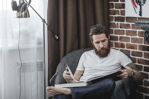 Man sitting on armchair looking at coffee-table book - VPIF00398