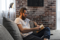 Man sitting on couch at home reading a book - VPIF00404