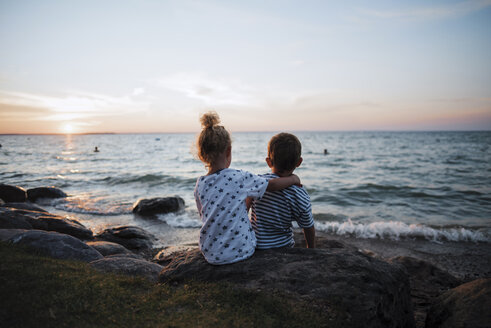 Rear view of siblings sitting on rocks by Lake Simcoe against sky during sunset - CAVF15341