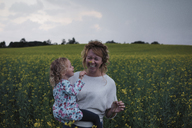 Daughter touching flower on cheerful mother's nose at field against sky - CAVF15347