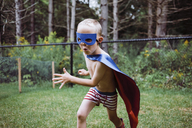 Playful shirtless boy wearing cape and eye patch while playing in yard - CAVF15365