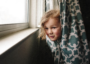 Playful girl peeking while hiding in curtain - CAVF15395