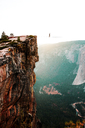 Distant view of person walking on rope tied to cliff at Yosemite National Park - CAVF15443