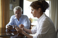 Couple using mobile phone while sitting at table - CAVF15494
