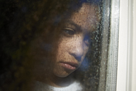 Sad girl looking away seen through wet window glass - CAVF15515