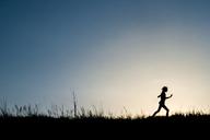 Silhouette girl running on grassy field against clear sky during dusk - CAVF15545