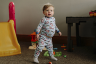 Portrait of baby boy standing on rug by toys at home - CAVF15560