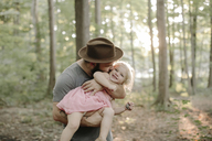 Father wearing hat kissing daughter while standing in forest - CAVF15587
