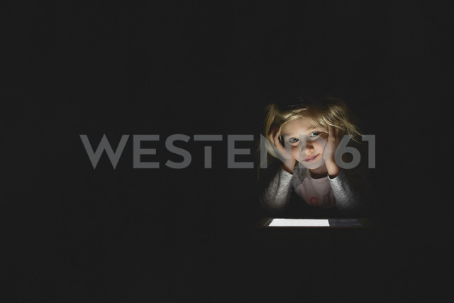 Bored girl using digital tablet while sitting in darkroom at home - CAVF15599