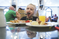 Playful girl having food at restaurant - CAVF15617