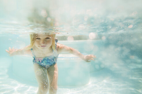 Girl swimming in pool on sunny day - CAVF15635