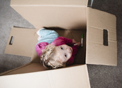 High angle view of playful girl sitting in cardboard box at home - CAVF15662