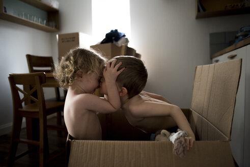 Brother kissing sister while sitting in cardboard box at home - CAVF15755