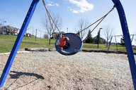 Boy playing on swing at park on sunny day - CAVF15770