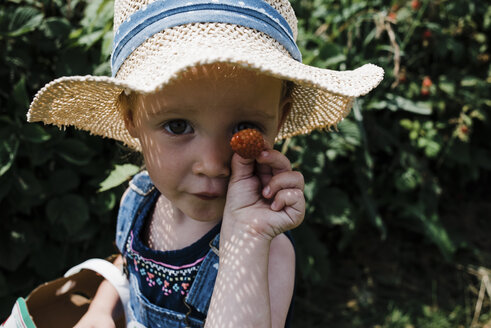 Portrait of girl showing raspberry while harvesting at farm - CAVF15815