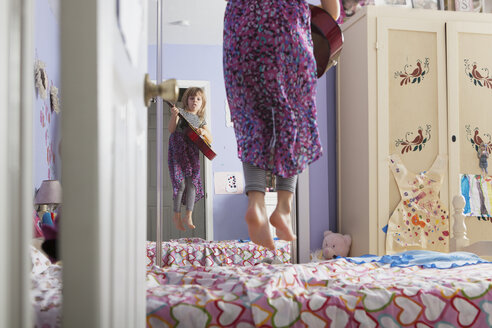 Girl holding guitar while jumping on bed in bedroom - CAVF15869