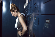 Tired sportswoman standing against lockers in gym - CAVF15884