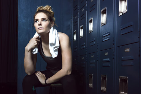Thoughtful tired sportswoman sitting by lockers in gym - CAVF15887