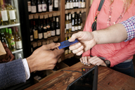 High angle view of small business owner taking credit card from customer at wine shop - CAVF15893
