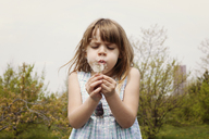 Cute girl blowing dandelion on field against clear sky - CAVF15974