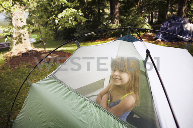 Portrait of smiling girl sitting in tent - CAVF15989