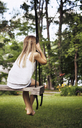 Rear view of girl sitting on swing at park - CAVF15998
