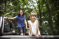 Sisters standing in pick-up truck against trees - CAVF16001