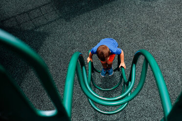 High angle view of boy playing on outdoor play equipment - CAVF16019