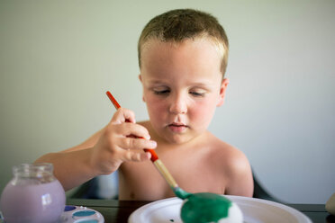Shirtless boy coloring egg while sitting by table at home - CAVF16022
