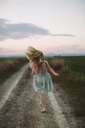 Rear view of girl running on dirt road during sunset - CAVF16166