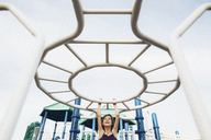 Playful girl hanging on jungle gym in playground - CAVF16211